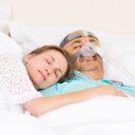 Mężczyzna śpiący w aparacie CPAP z kobietą u boku