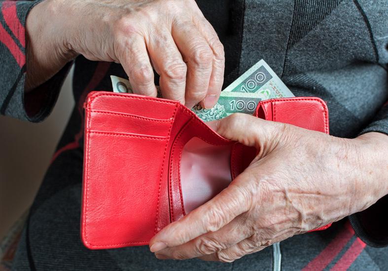 Zdjęcie dłoni starszej osoby sięgającej doportfela