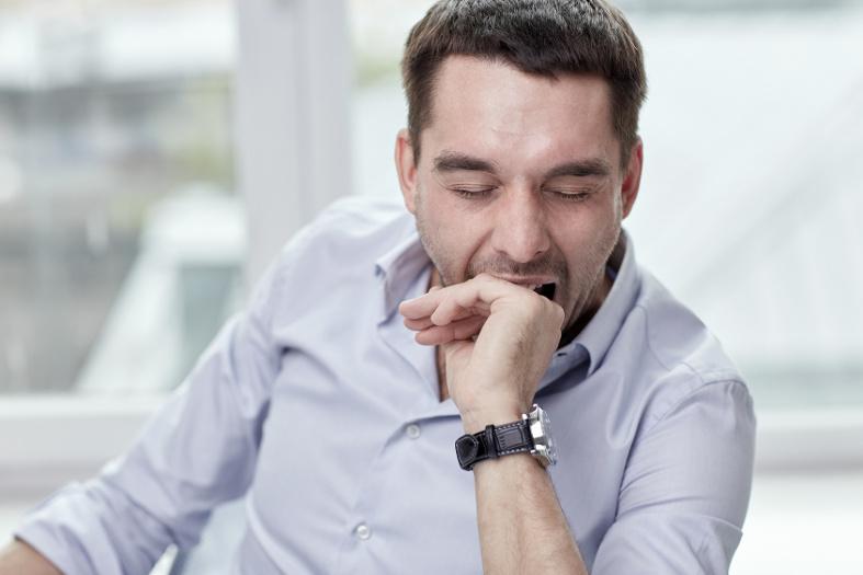 Zmęczony mężczyzna jest senny iziewa - może toobturacyjny bezdech senny