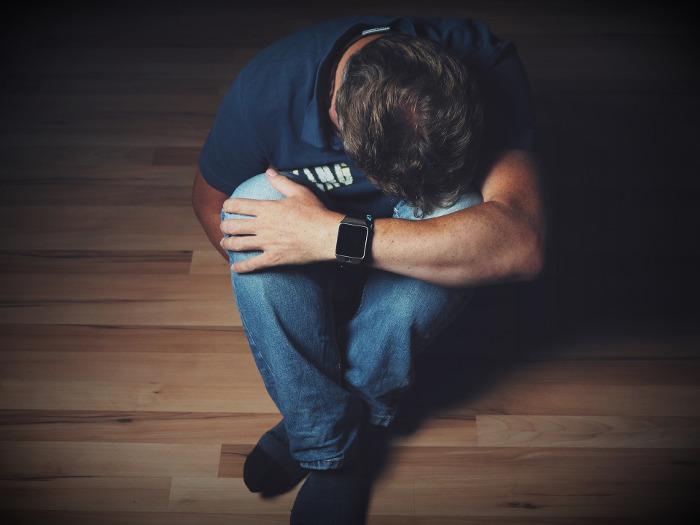 Cierpiący-na-depresję-mężczyzna-siedzi-skulony-na-podłodze-Bezdech-śródsenny-senny-może-być-jego-przyczyną.jpg