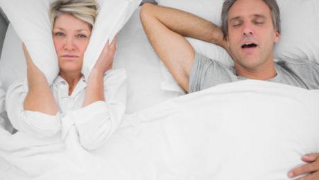 kobieta zakrywa poduszką uszy bo nie może spać z uwagi na chrapanie partnera w łóżku