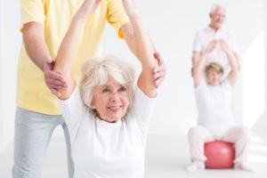 Seniorzy ćwiczą podokiem rehabilitantów