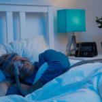 Śpiący mężczyzna w masce CPAP do terapii bezdechu sennego