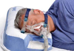 Dobór aparatu CPAP torównież dobór akcesoriów. Mężczyzna śpi napoduszce doCPAP