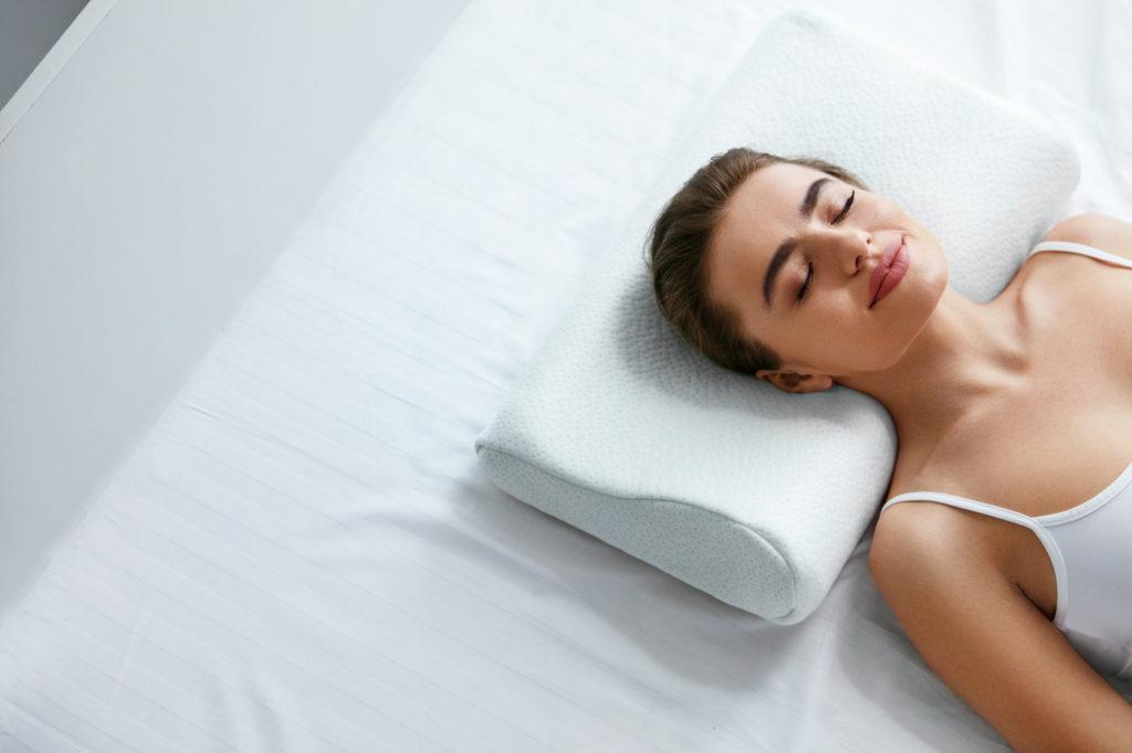 Kobieta śpi wpozycji naplecach napoduszce specjalistycznej