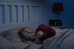 Mężczyzna śpi wCPAP. Połączenie alkoholu ibezdechu sennego niestanowi przeszkody wużywaniu CPAP.