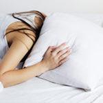 kobieta zakrywa poduszką głowę bo odczuwa szum w uszach